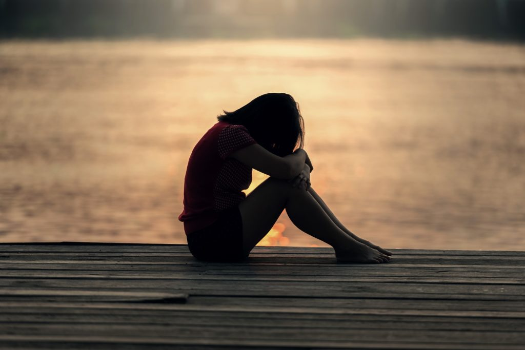 Jente - trist - sitter på en brygge.