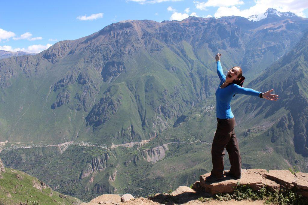 Kvinne som står på en murkant og skuer utover dal og fjell. Hun har armene ut og er tydelig glad.