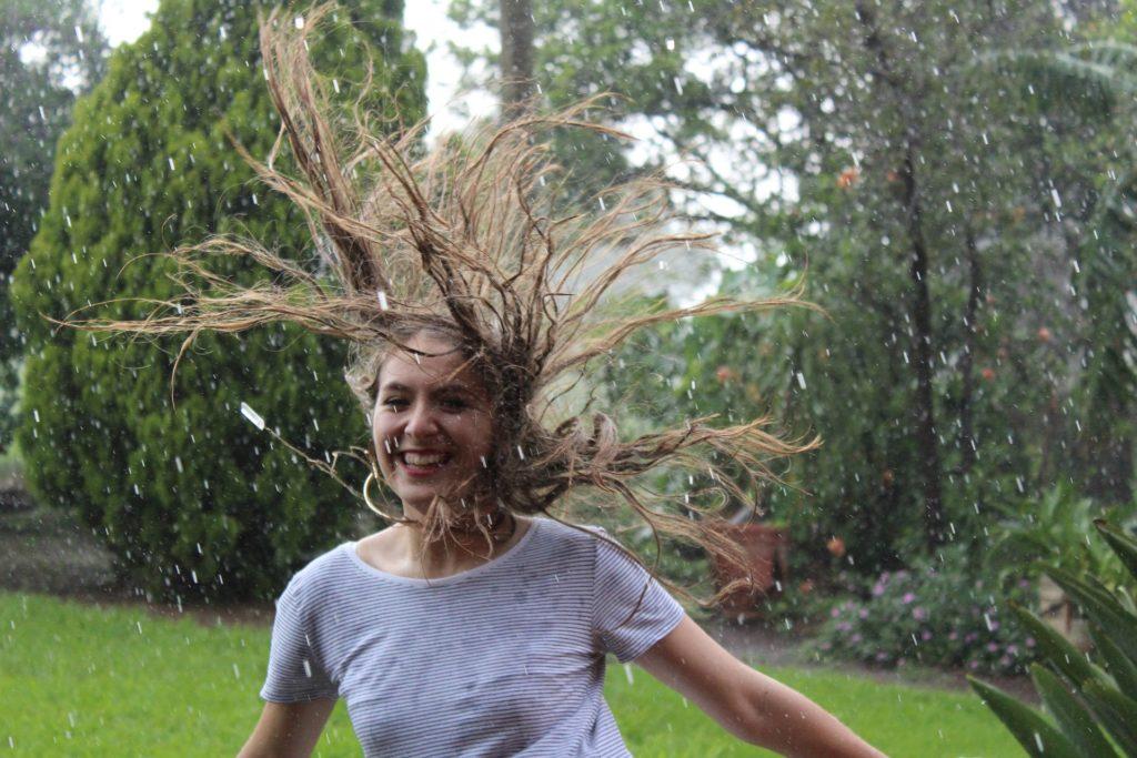 Kvinne som ler og danser i regnet.