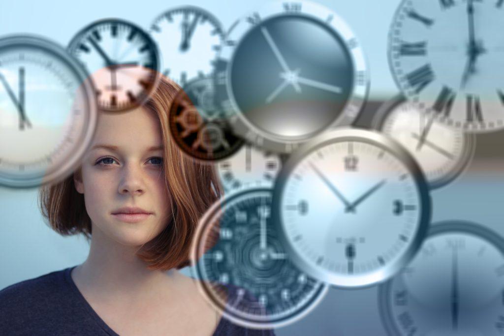 En kvinne med alvorlig ansikt og mange ur-skiver.