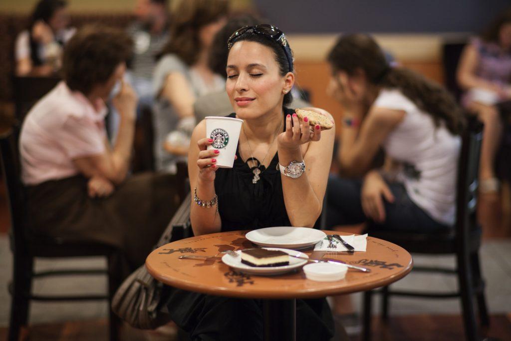 Kvinne på kafé, som nyter kaffe og noe og bite i. Ansiktet uttrykker at hun virkelig koser seg. Hun vet å nyte de gode stundene.