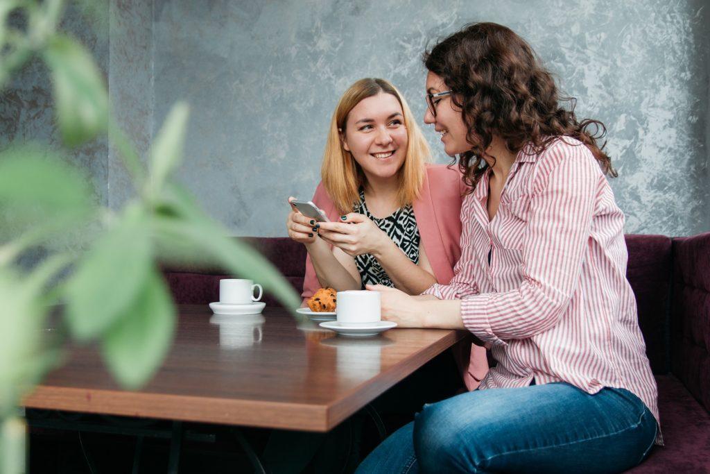 De to samme kvinnene som forrige bilde, men denne gangen smiler de og deler noe som de ser på telefonen.