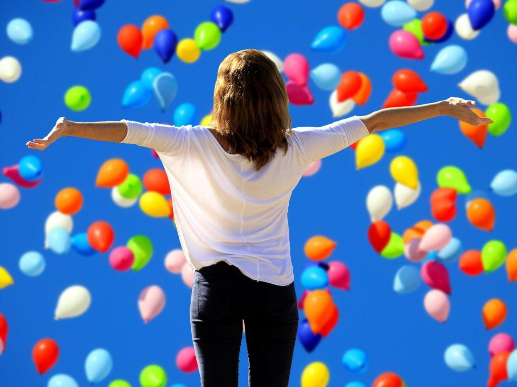 """Dame som står med ryggen til og armene ut - hun sier """"Ja til livet"""". Hun er omgitt av ballonger i mange farger."""