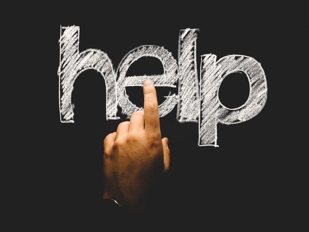 """En tavle med ordet """"Help"""" skrevet med kritt i tykke bokstaver. Det henspeiler på at man av og til trenger hjelp for å skape nye vaner gjennom affirmasjoner og positive gjentakelser."""