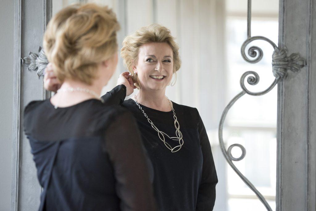 En flott, voksen dame som ser på seg selv i speilet og smiler. Det er en god morgenrutine.