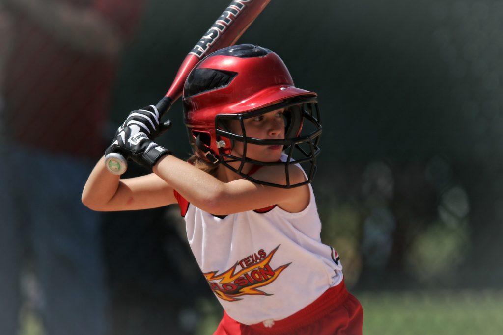Et barn som spiller softball, og som står klar til å slå. Dyp konsentrasjon og stort fokus.
